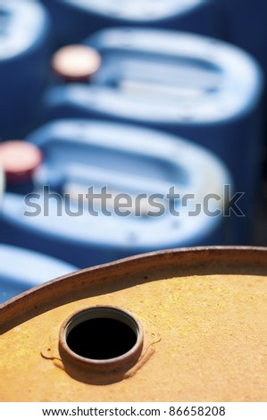 Old colored barrels for oil products. Empty rusted drums and blue canisters - stock photo