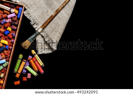 Old colorful art pastel crayons on black background