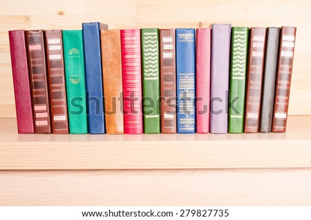 Old colorful books on wooden shelf