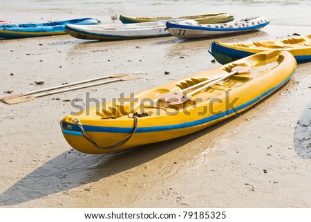 Old Colorful kayaks on the beach - stock photo