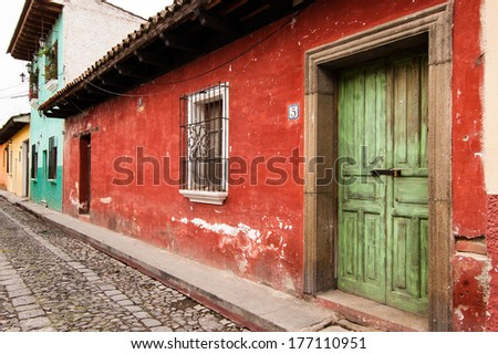 Old, colorful painted houses along cobbled street in colonial city of Antigua in Guatemala - stock photo