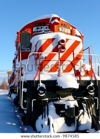 Old colorful red and white striped train outdoors in winter