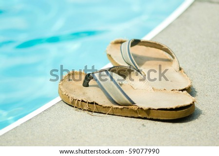 Old, comfortable sandals by the pool - stock photo