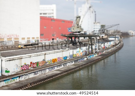 Old commercial dock at river Rhine at Basel. Selective Focus with Tilt/Shift-Lens on the colorful graffities. - stock photo