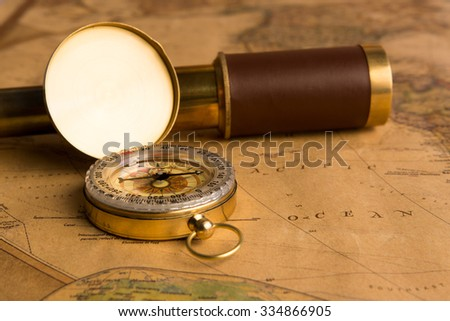 Old compass and old telescope on vintage map