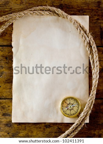 old compass and rope on vintage paper - stock photo