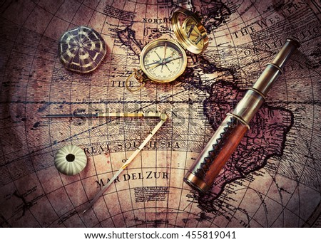 Old compass and telescope on vintage map. Retro style. - stock photo