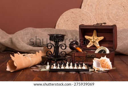 Old compass lying on antique map with treasure chest, knife, money,globe and chess - stock photo