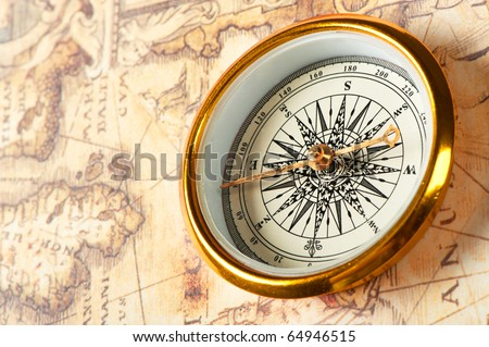 Old compass on ancient map. A compass with the antique image of a direction - stock photo