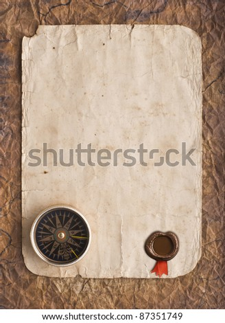 old compass on grunge background with a wax seal  and ribbon - stock photo