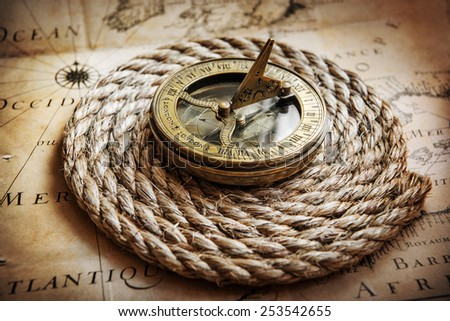 Old compass on vintage map. Adventure stories background - stock photo