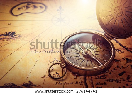 Old compass on vintage map. Retro stale. - stock photo