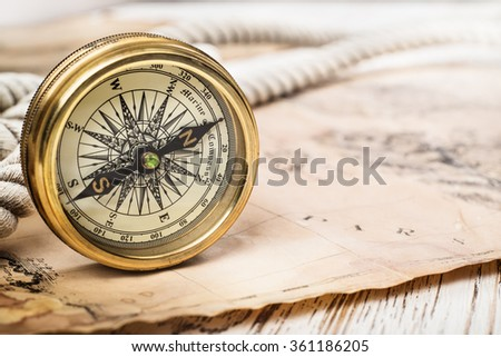 Old compass on vintage map. Retro stale. Very shallow focus. - stock photo