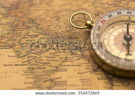 Old compass on vintage map selective focus on India - stock photo
