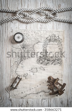 old compass, rope, vintage map, sextant on old wood desk. - stock photo