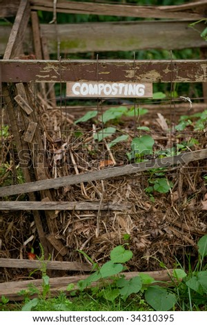 old composting bin with vines growing on it and a composting sign - stock photo