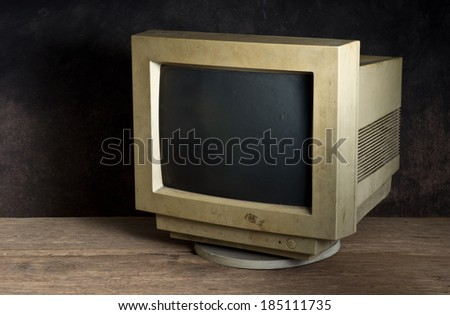 old computer monitor on old wood table on dark background - stock photo