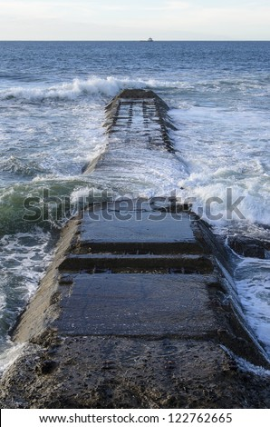 Old concrete structure protecting waste pipes going into the sea at Moulle Point in Cape Town South Africa - stock photo