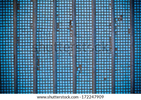 Old concrete wall with blue mosaic of small size.Photo closeup