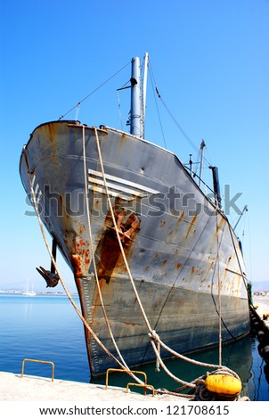 Old container ship docked in port - stock photo