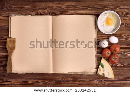 old cook book, the ingredients for a meal on a background of vintage wood - stock photo