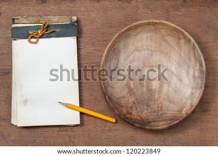 Old cookbook and wood plate on wooden texture background - stock photo
