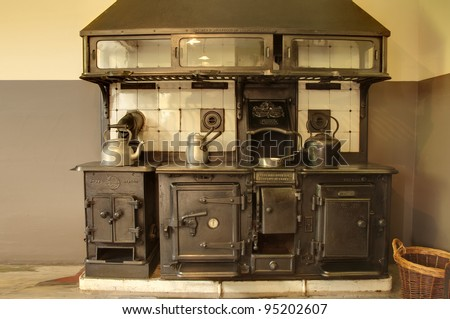 Old cooker with kettles and pans - stock photo