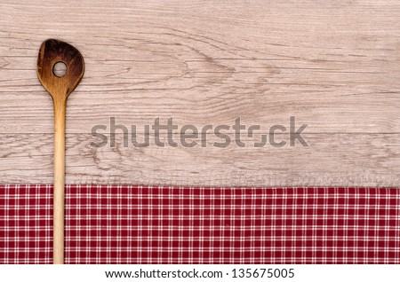 Old cooking spoon on checkered table cloth and wooden board - stock photo