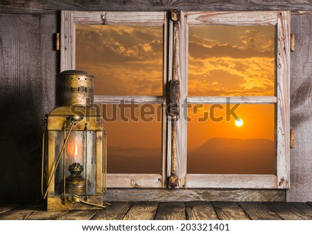 Old copper lantern on Windows sill: view outdoor when the sun rise up. Concept for dreams, feelings or mourning. - stock photo