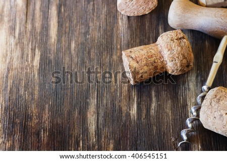 Old corkscrew for wine and wine corks on a vintage wooden background. Close-up. Toned image. Selective focus. Copy space background - stock photo