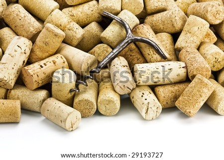 Old corkscrew on a heap of wine stoppers - stock photo