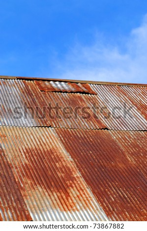 Old corrugated tin roof is rusting and patched.  Sunny blue sky and wispy clouds frame building. - stock photo