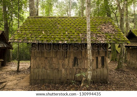 Old cottage, old wooden house, with moss among trees - stock photo