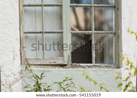 old cottage window with broken window pane and flaking paint
