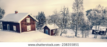 old cottages in a rural snowy winter landscape typical of Sweden - stock photo