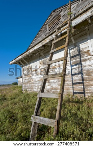 Old country building with peeling pain and ladder - stock photo