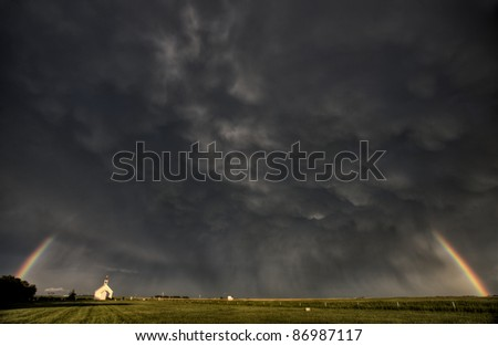 Old Country Church in Saskatchewan Canada with storm clouds rainbow - stock photo