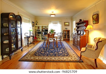Old country English charm living and dining room with blue rug. - stock photo