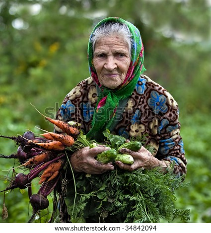 Old country lady with vegetables - stock photo