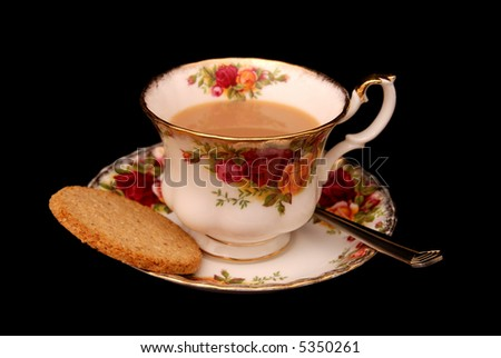 Old country roses cup and saucer with English tea and biscuit on black background