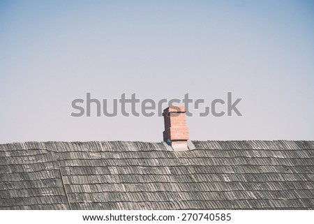 old countryside house with brick chimney and wooden roof - retro vintage film effect - stock photo