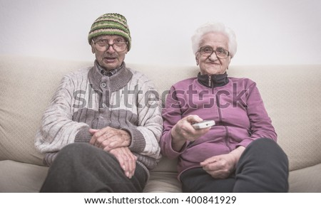 Old couple and zapping. senior couple watching television on the couch - stock photo