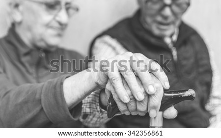 Old couple holding each others hands on the cane