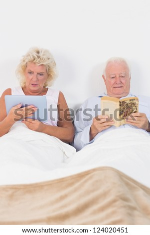 Old couple reading or using a digital tablet on the bed