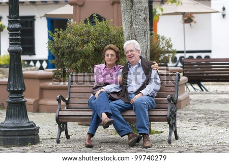 Old Couple Sitting On Bench In Park - stock photo