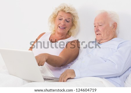 Old couple using a laptop on the bed - stock photo