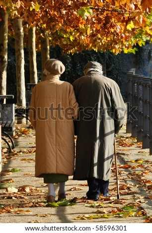 Old couple walking along an autumn path arm in arm - stock photo