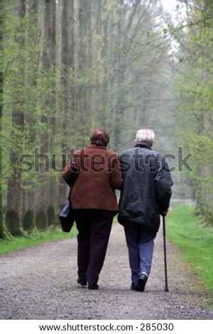 old couple walking in a forest - stock photo