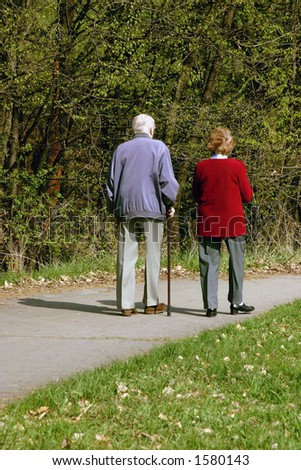 Old couple walking together in park - stock photo