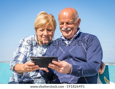 old couple watching photos on a tablet - stock photo